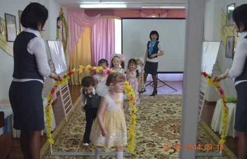 Дети строятся за воспитателем и проходят через воротики